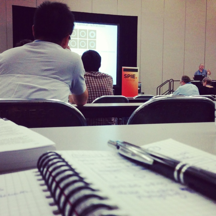 Taking notes at a SPIE talk.